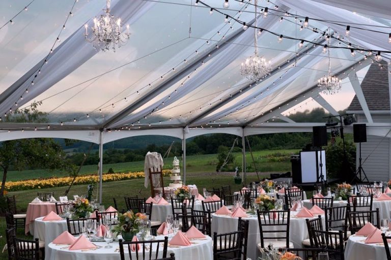Clear top tent with ceiling lighting over guest tables with wooden chairs