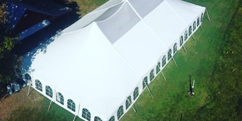 Birds eye view of a large white tent setup in a green field