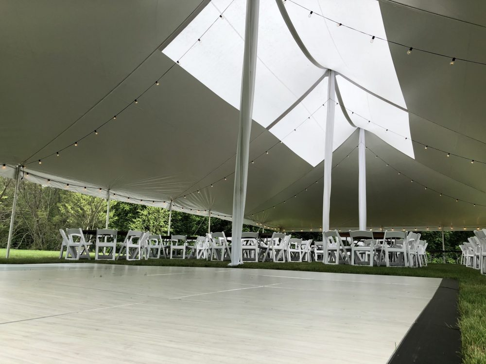 White pole tent with clear top section overlooking white chairs & tables and a dancefloor