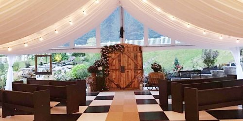 Wedding tent with elegant tent lighting above wooden pews and stand-alone barn doors
