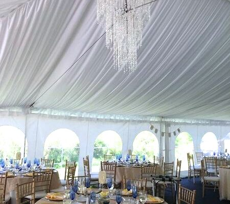 Elegant tent liner and chandeliers over a copper-colored guest table setup